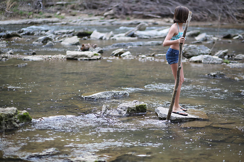 Girl Walking Across A River by ALICIA BOCK for Stocksy United