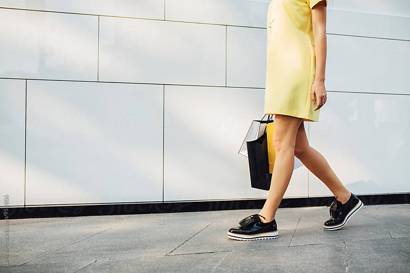 Woman in Yellow Dress Carrying Shopping Bags by Lumina for Stocksy United