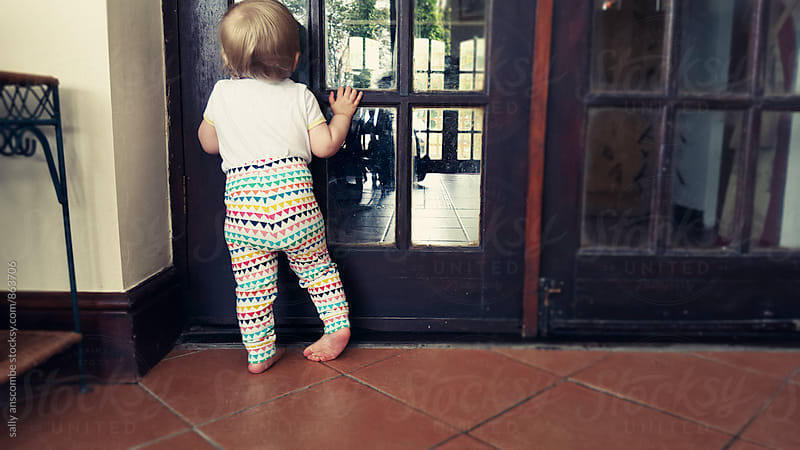 Toddler girl peeping through a window by sally anscombe for Stocksy United