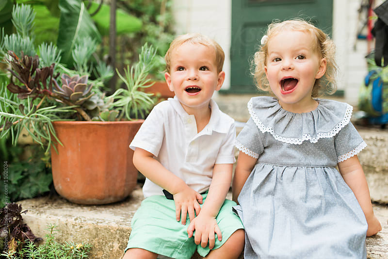 Two young twins playing outside in the summertime by Chelsea Victoria for Stocksy United