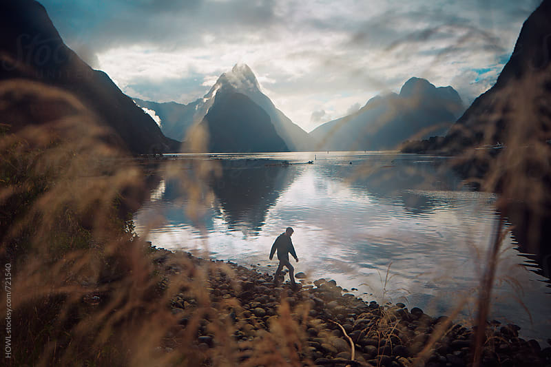 a man walking across the rocky shores of New Zealand  by HOWL for Stocksy United