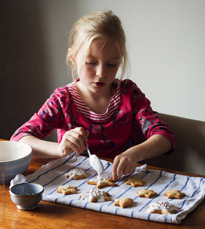 A little girl decorating home-baked star cookies by Helen Rushbrook for Stocksy United