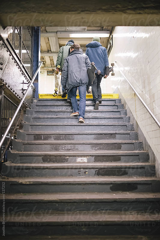 Young Men Friends Navigating Intricate Paths and Stairs of New York Subway by Joselito Briones for Stocksy United