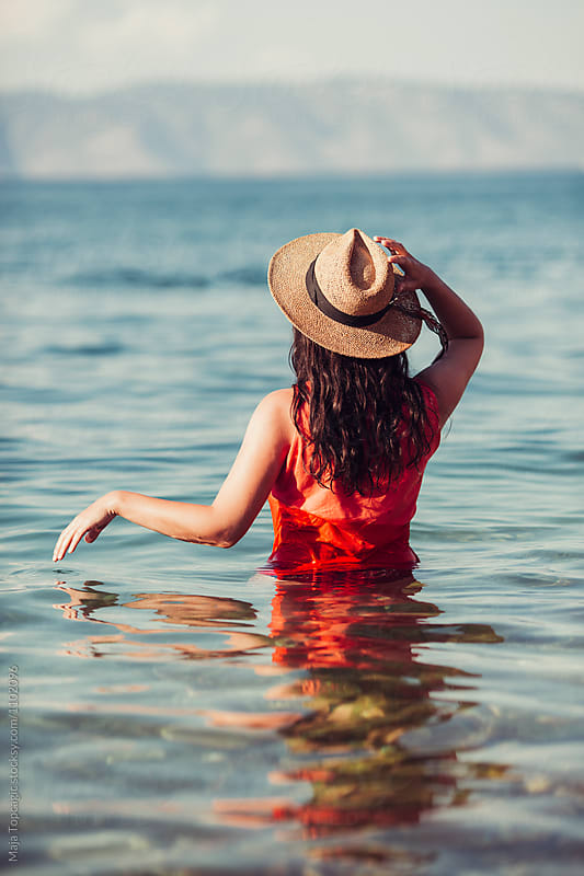 Woman from behind in the sea by Maja Topcagic for Stocksy United