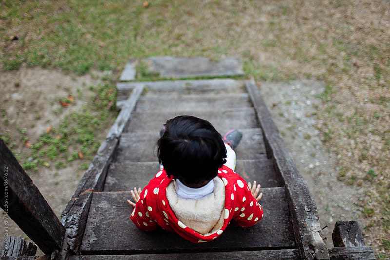 top view of child sitting on wooden steps by Saptak Ganguly for Stocksy United