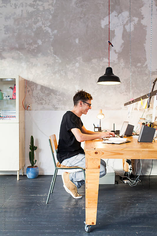 Entrepreneur or professional working behind his laptop in his office by Ivo de Bruijn for Stocksy United