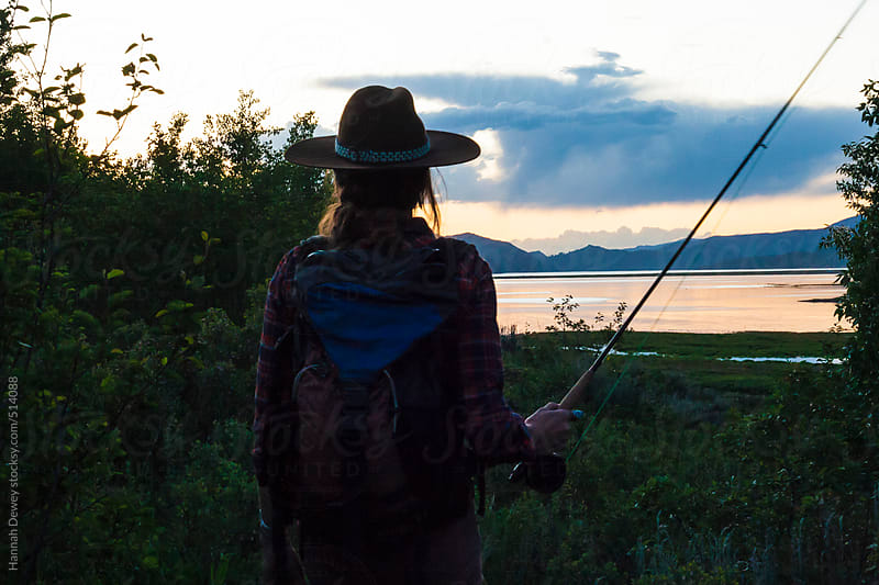 Woman walks home after fly-fishing on a summer evening by Hannah Dewey for Stocksy United