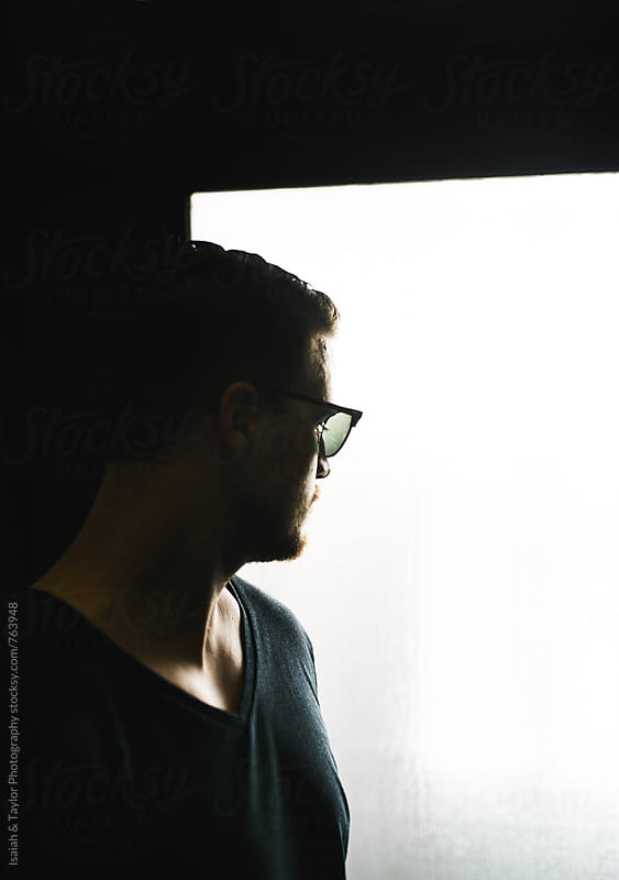 Man looking out a window by Isaiah & Taylor Photography for Stocksy United