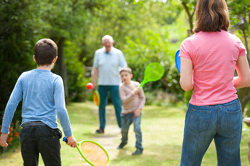 grandfather mother and boys playing tennis together by Lee Avison for Stocksy United