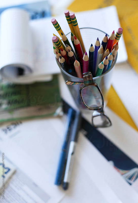 Pencils in a cup on a desk with papers and a pair of glasses by Carolyn Lagattuta for Stocksy United