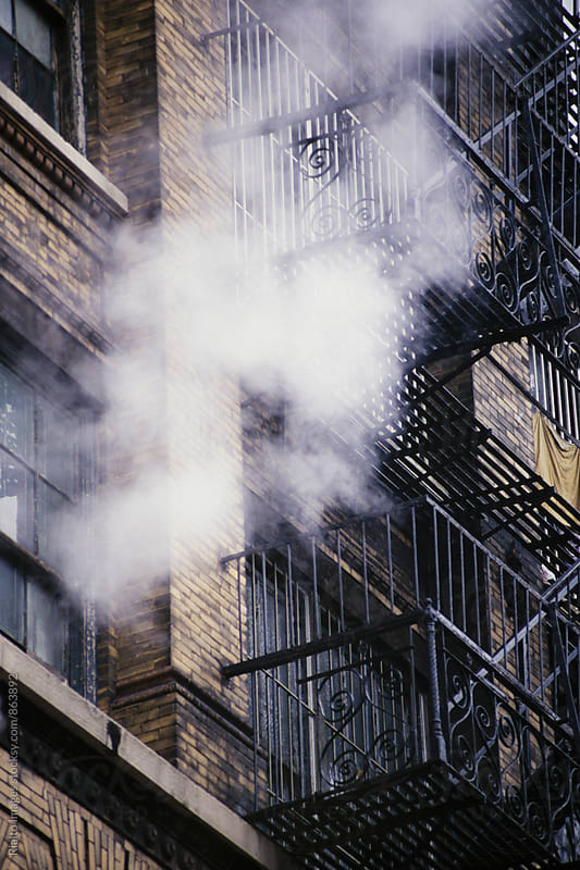 Steam rising above apartment building and fire escape, NY, NY, USA by Paul Edmondson for Stocksy United