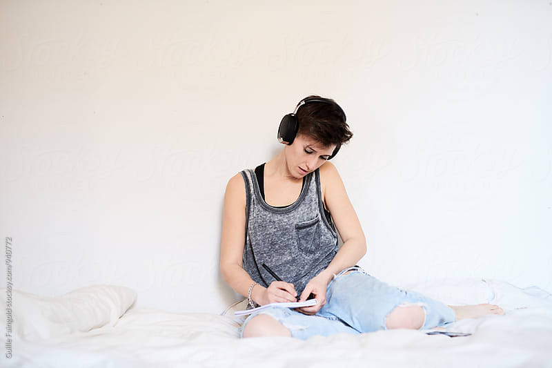 Woman sitting on bed in headphones  by Guille Faingold for Stocksy United