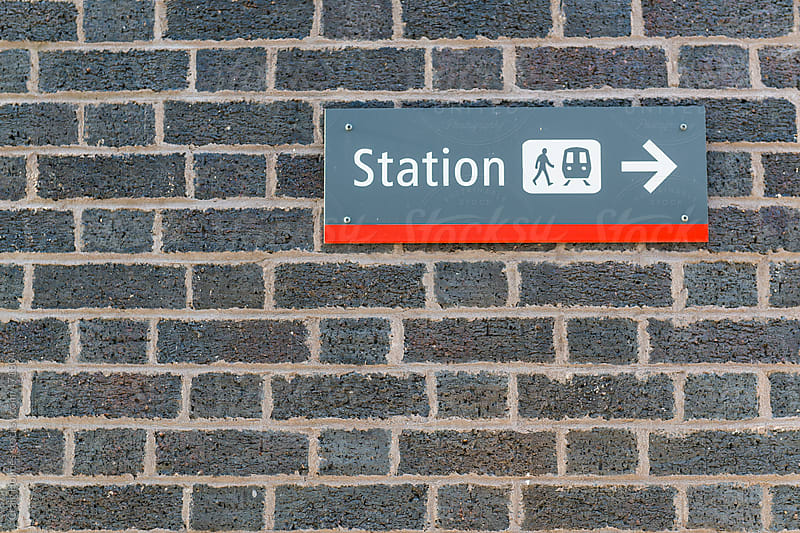 Sign pointing the direction to a railway station by Craig Holmes for Stocksy United