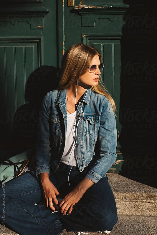 Beautiful Blond Woman Sitting In Front of the Green Door by Katarina Radovic for Stocksy United