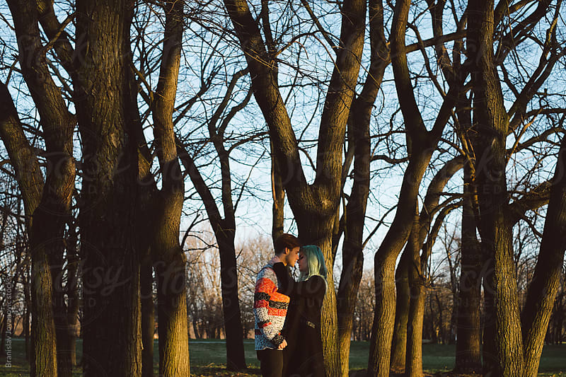 Young couple in love standing in the woods by Brkati Krokodil for Stocksy United
