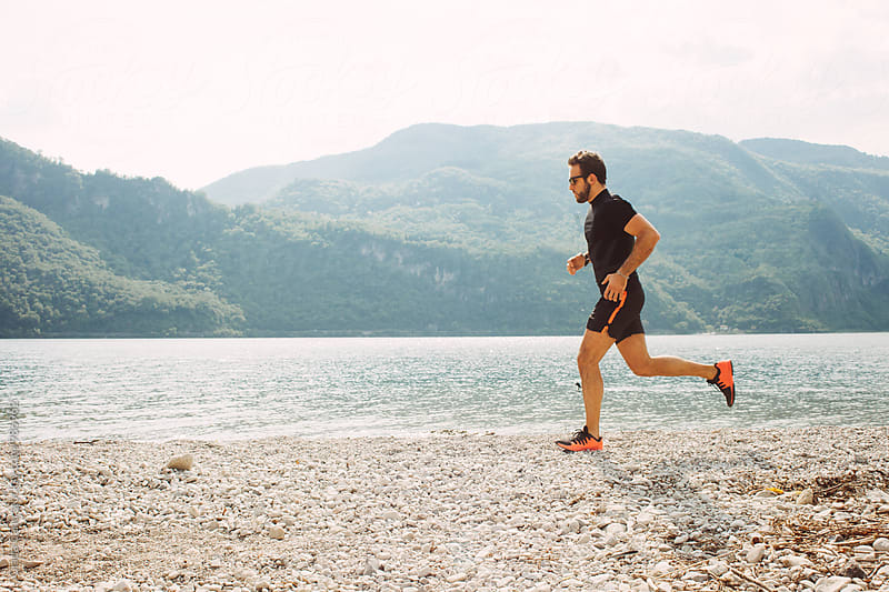 Man running by the lake by Giada Canu for Stocksy United