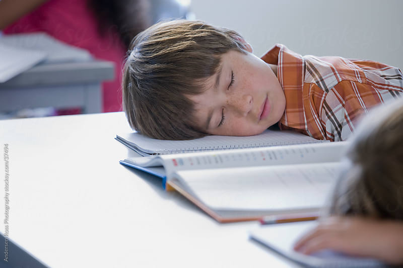 Boy (10-11) sleeping on desk in classroom by Andersen Ross Photography for Stocksy United