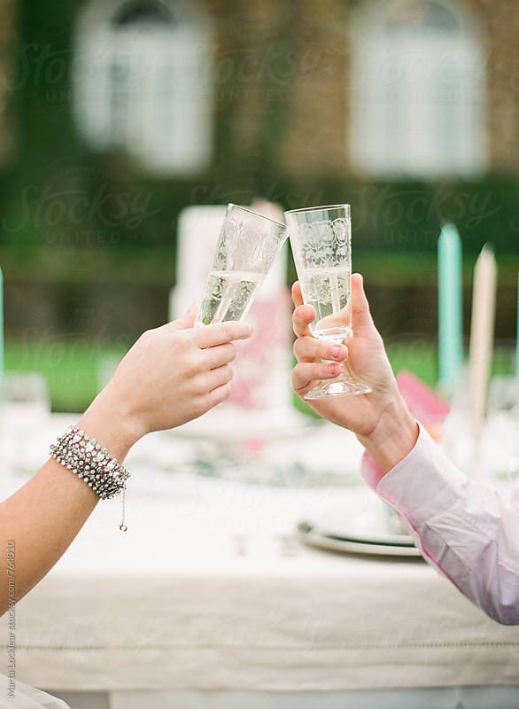 Bride and groom toasting by Marta Locklear for Stocksy United