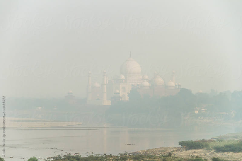 taj mahal on the river yamuna descends into smog by Leander Nardin for Stocksy United