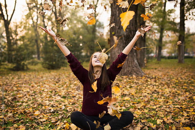Young woman throwing leaves in the air by Jovana Rikalo for Stocksy United