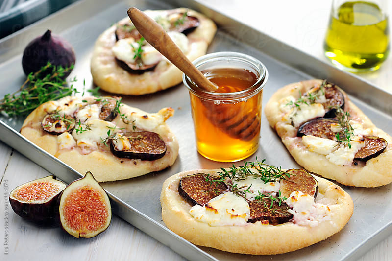 Food: Small Pizza with Figs, Goat cream cheese, Thyme and Honey by Ina Peters for Stocksy United