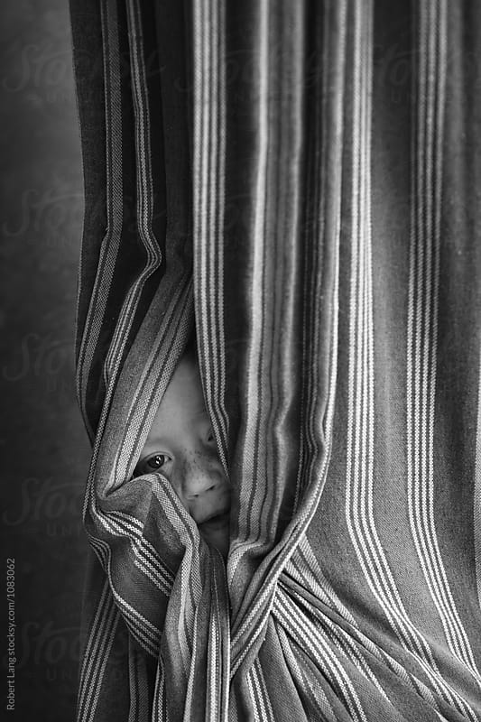 Child wrapped up in a hammock by Robert Lang for Stocksy United