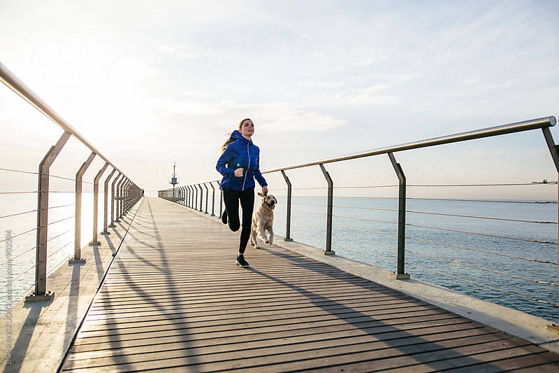 Woman running with her dog on the bridge at morning. by BONNINSTUDIO for Stocksy United