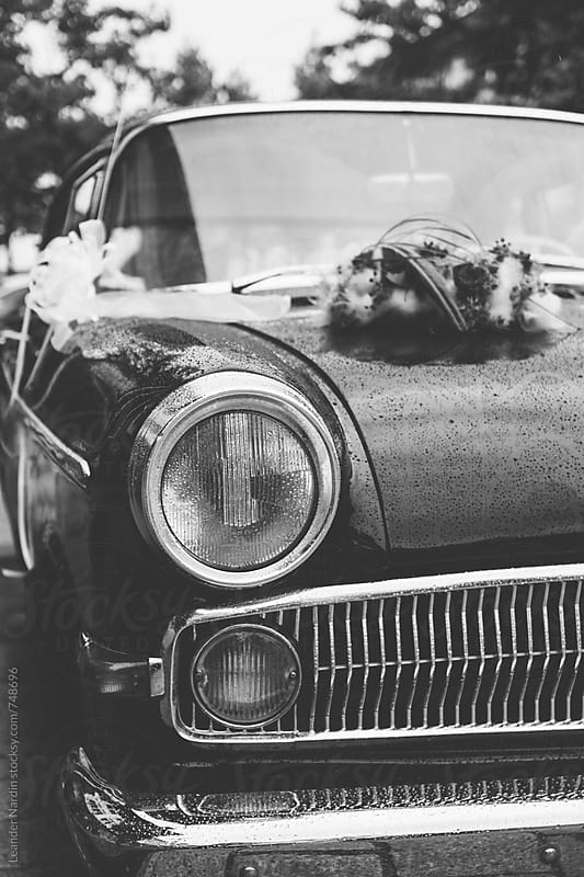classic oldtimer car with wedding flowers on the hood in black and white by Leander Nardin for Stocksy United