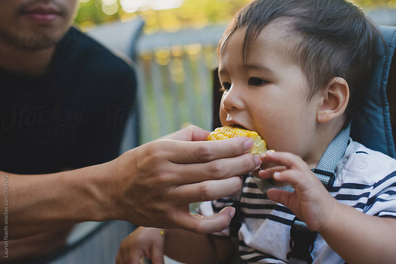 Dad feeding baby corn on the cob by Lauren Naefe for Stocksy United