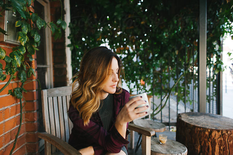 A Pretty Girl Drinks Coffee by Caleb Thal for Stocksy United