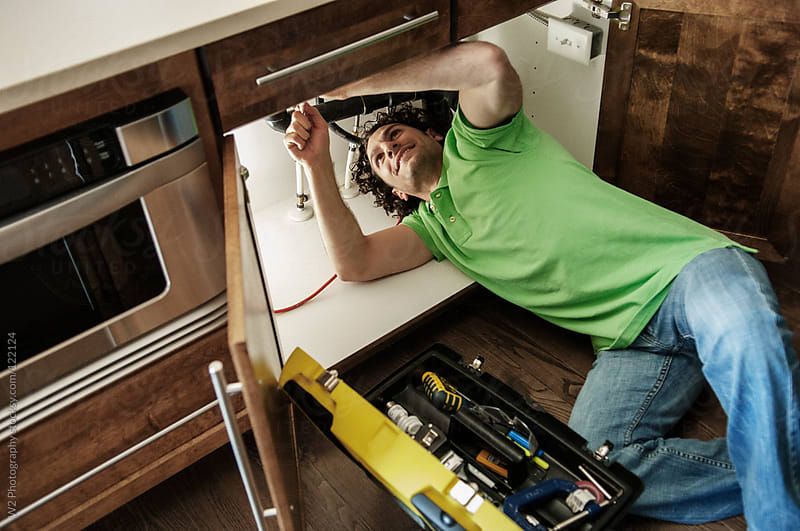 Handyman working on sink in the kitchen by W2 Photography for Stocksy United