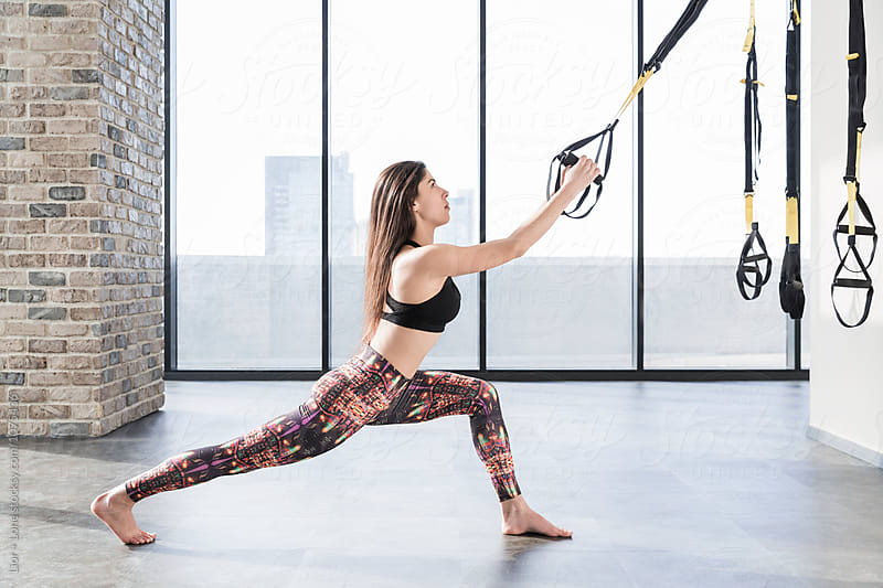 Young athletic woman training with straps indoors  by Lior + Lone for Stocksy United