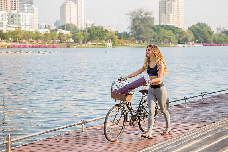 Beautiful young woman pushing her bicycle on her way to a yoga practice by Jovo Jovanovic for Stocksy United