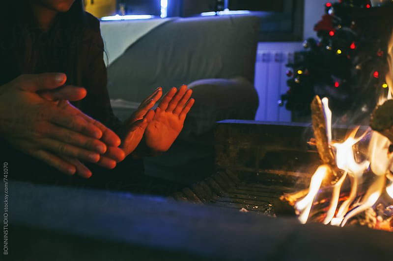 Hands of a couple warming up in front of a fireplace at home. by BONNINSTUDIO for Stocksy United