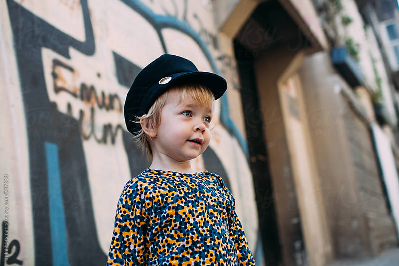 Toddler girl in hat with graffiti behind her. by Julia Forsman for Stocksy United