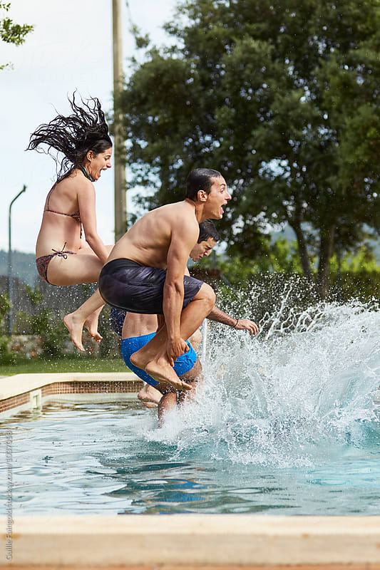Adults jumping in pool by Guille Faingold for Stocksy United