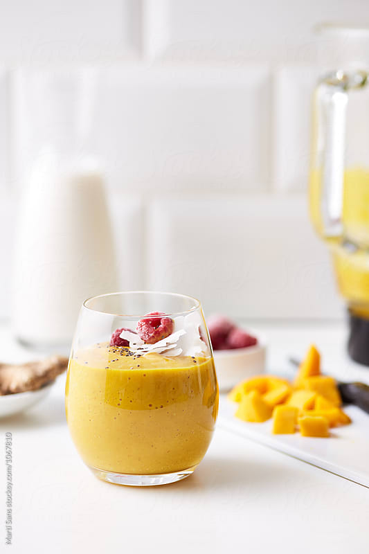 Delicious yellow fruit smoothie by Martí Sans for Stocksy United