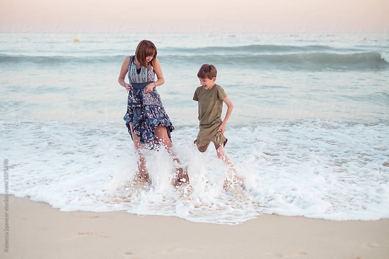 Fully clothed family caught by sea waves by Rebecca Spencer for Stocksy United