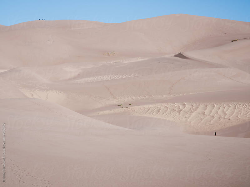 Small anonymous people hiking giant sand dunes by Jeremy Pawlowski for Stocksy United