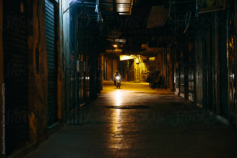 Dark alley with a moped in the back by Alejandro Moreno de Carlos for Stocksy United