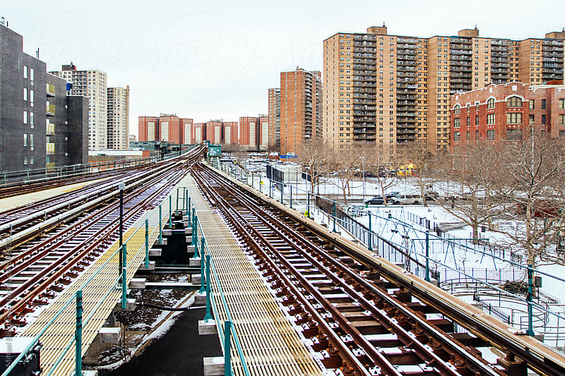 Aboveground subway lines with apartment buildings in a city in the winter by Mihael Blikshteyn for Stocksy United