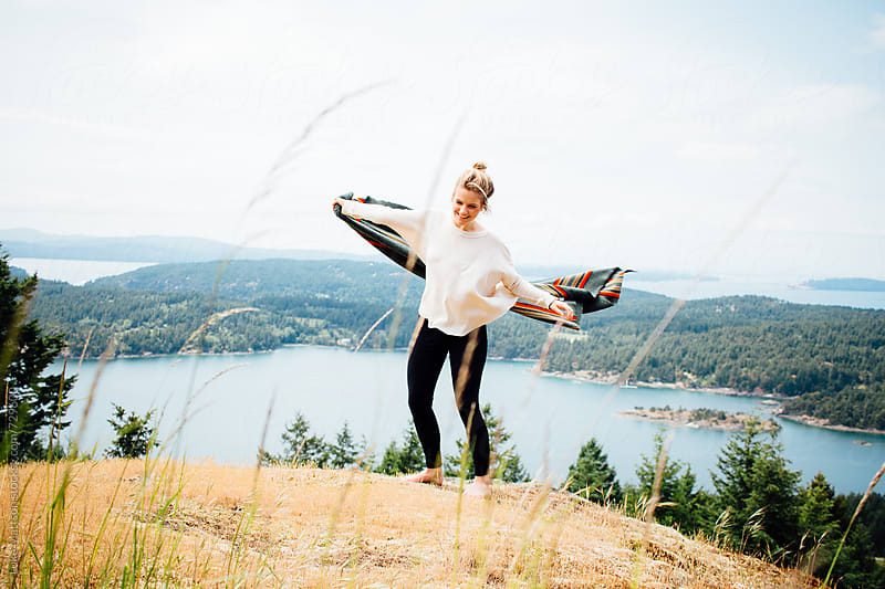 Young Blonde Woman Spinning With Wool Blanket On Forest Island Hillside by Luke Mattson for Stocksy United