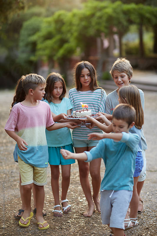 Group of children carefully carrying a birthday cake by Miquel Llonch for Stocksy United
