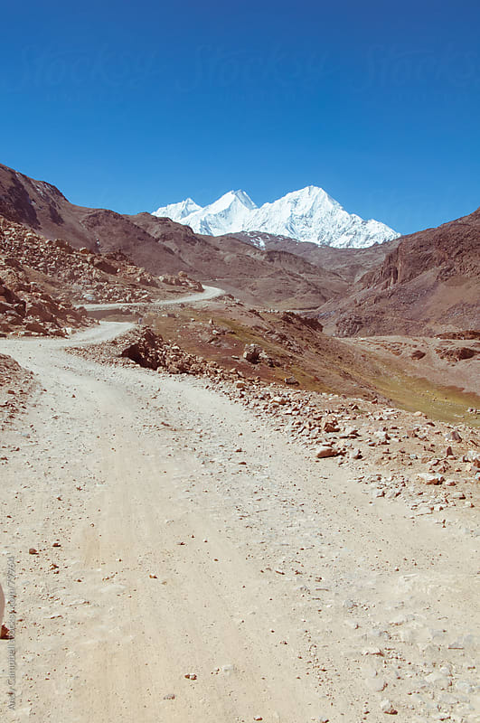 A rough dirt track leading through a valley to the Himalayas by Andy Campbell for Stocksy United