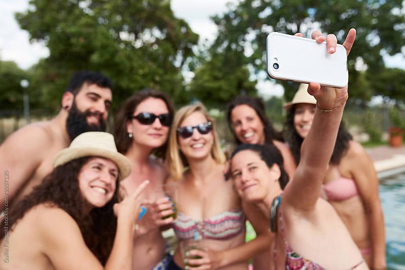 Happy friends making selfie near pool in garden by Guille Faingold for Stocksy United