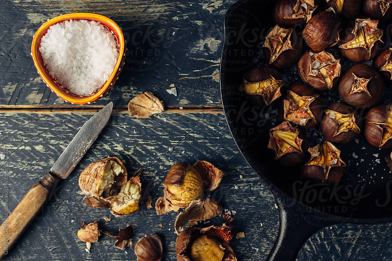 Roasted chestnuts in a cast iron skillet by Gabriel (Gabi) Bucataru for Stocksy United