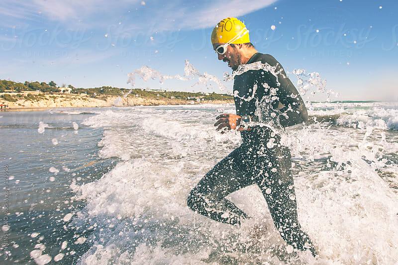 Triathlete running in to the water on triathlon race. Splashing water. by BONNINSTUDIO for Stocksy United