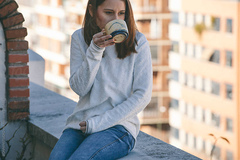 Young woman drinking a coffee in the terrace. by BONNINSTUDIO for Stocksy United