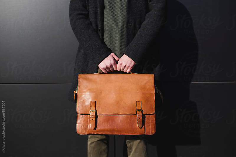 Male hands holding a briefcase by michela ravasio for Stocksy United