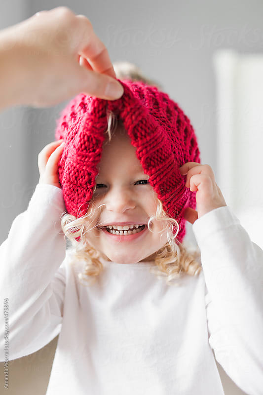 Smiling young girl with blond curly hair wearing red winter hat by Amanda Worrall for Stocksy United